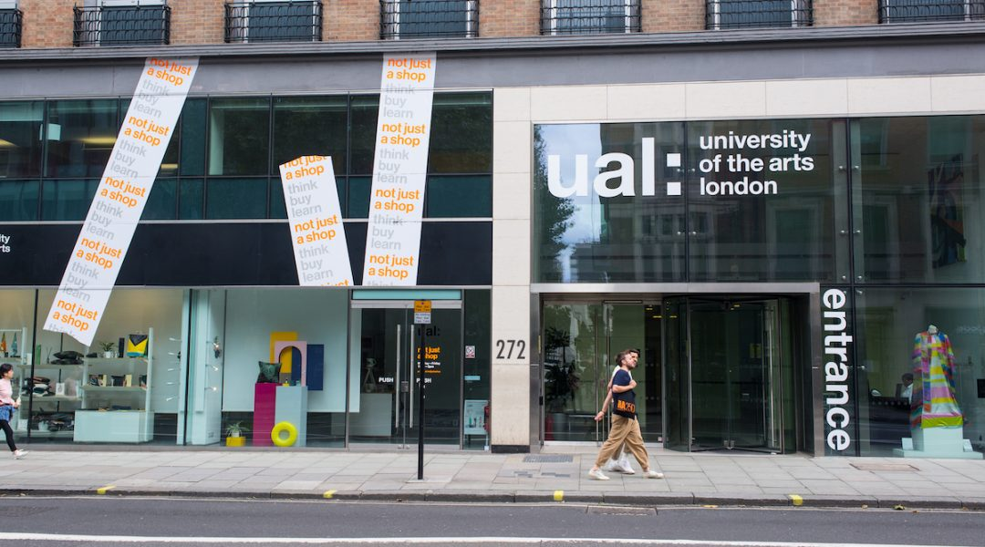 London, UK - August  2019: Men couple students walking in front of the main entrance of ual, University of the arts london, in High Holborn, London